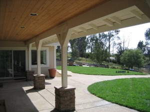 Back porch view of the total house rebuild. Wrap around covered porch with recessed lighting and stone wrapped columns. Sand finish exposed aggregate concrete with integral color and an easy to look at serpentine design for the patio layout.