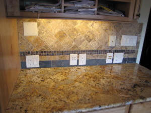 Custom backsplash with tumbled marble stone tile and slate tile and granite countertop